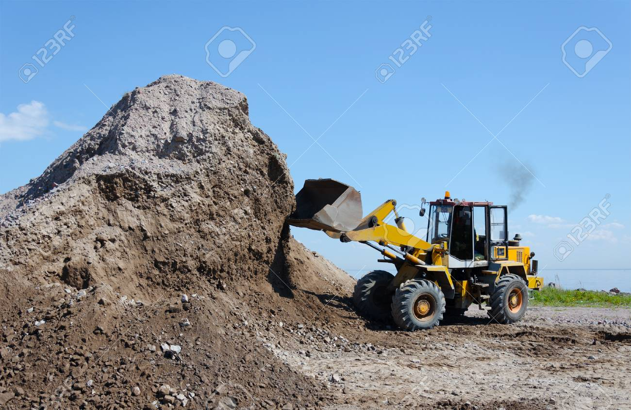 Wheel excavator digging gravel pile for loading in the truck - 95195740