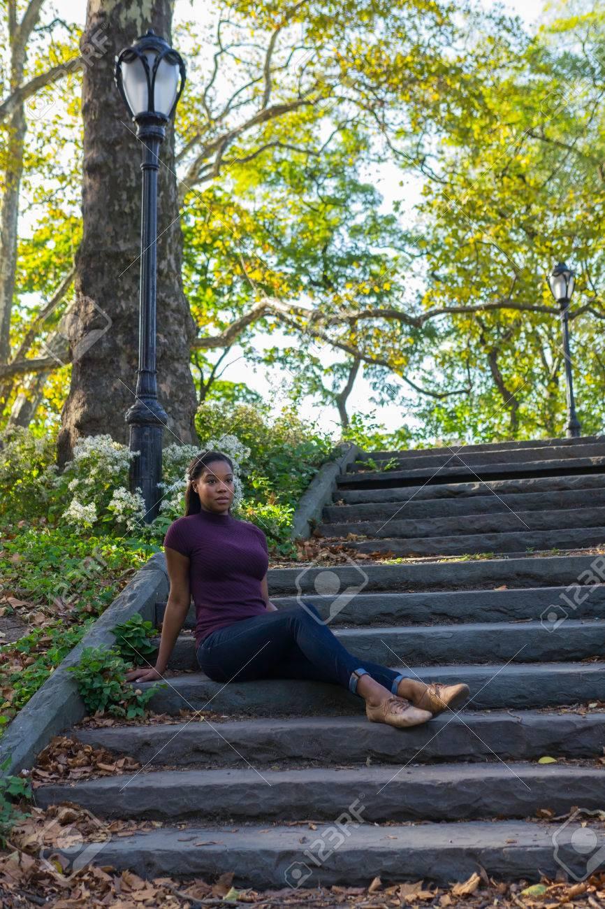una mujer sentada en los escalones de piedra en un parque foto de archivo