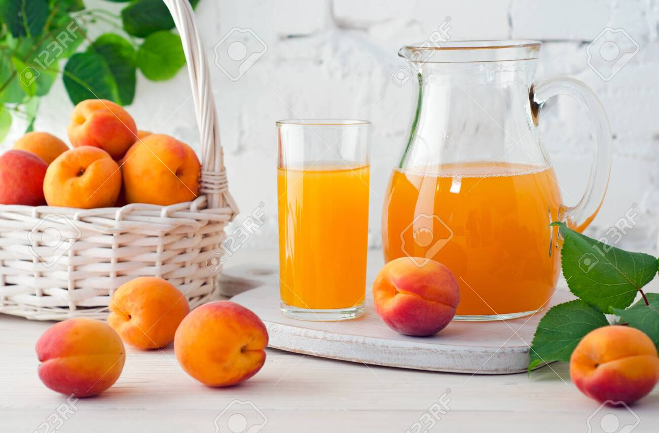 Apricot juice in glass and decanter with ripe apricots on wooden table on background of white brick wall with green leaves. - 138321897