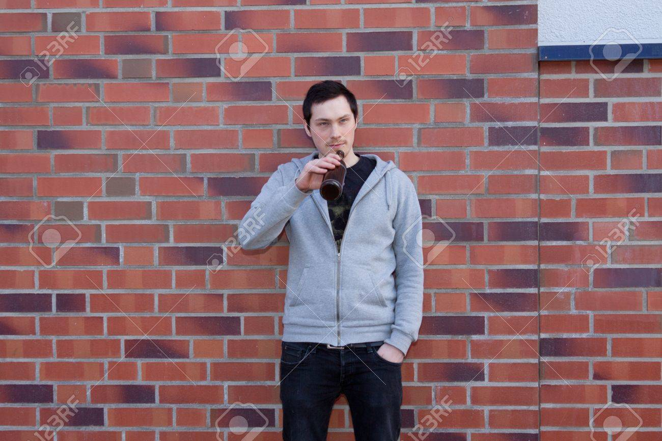 A young man is standing in front of a wall drinking beer Stock Photo - 9216549