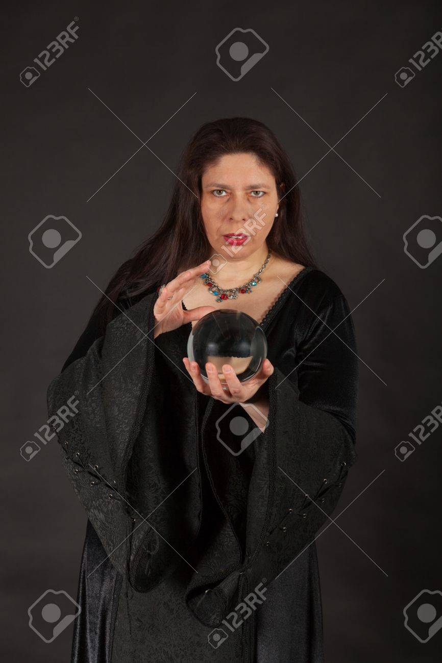 A dark dressed woman is looking into a crystal ball Stock Photo - 16326281