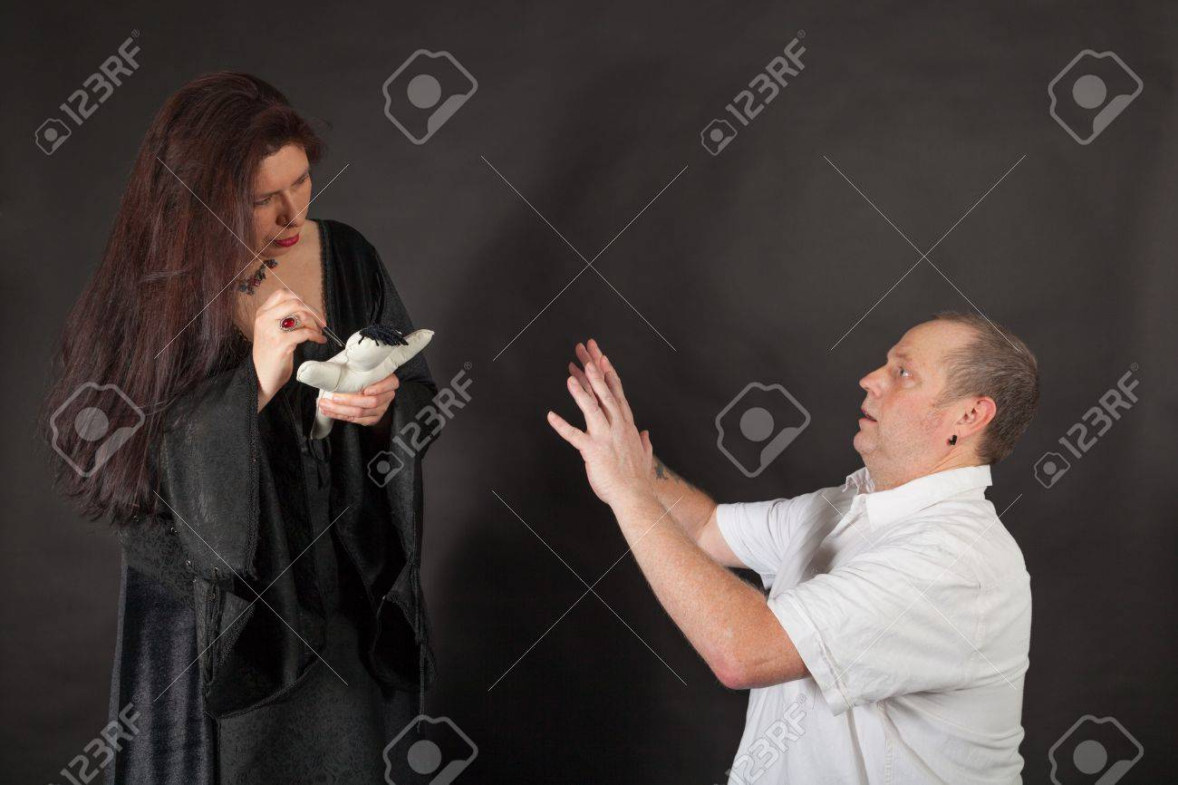 A dark dressed woman is stabbing a doll with a needle Stock Photo - 16326245