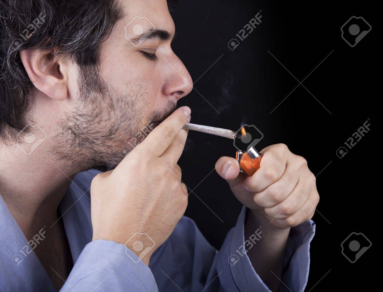 Closeup of an adult man (30 years old) with his profile to the camera. He appears to be quite a bum, being unshaved and wearing a light blue fabric robe, concentrated in lighting a marijuana jspliff (aka reefer; joint) with a simple disposable half-transp Stock Photo - 19281635