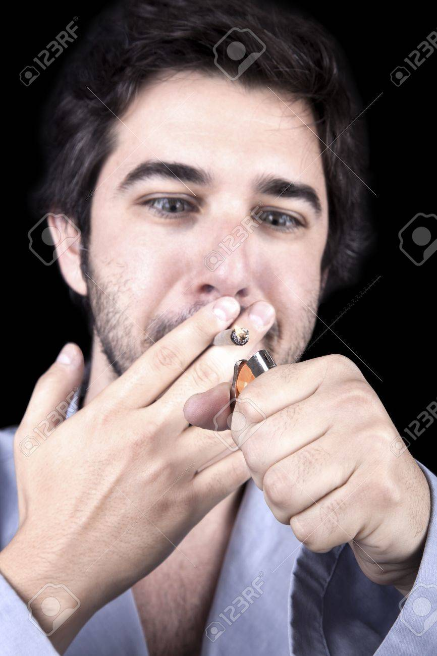 Closeup of an adult man (30 years old), which  appears to be quite a bum, being unshaved and wearing a light blue fabric robe; looking extremely delighted as he is about to start smoking a marijuana spliff (aka reefer; joint) at which he's watching with a Stock Photo - 19281633