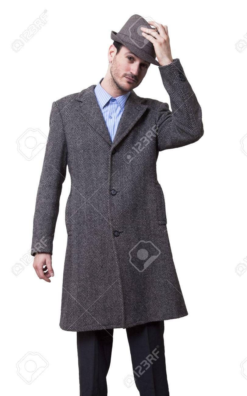 Ein Mann im Mantel und Hut mit einem Stock in der Hand auf