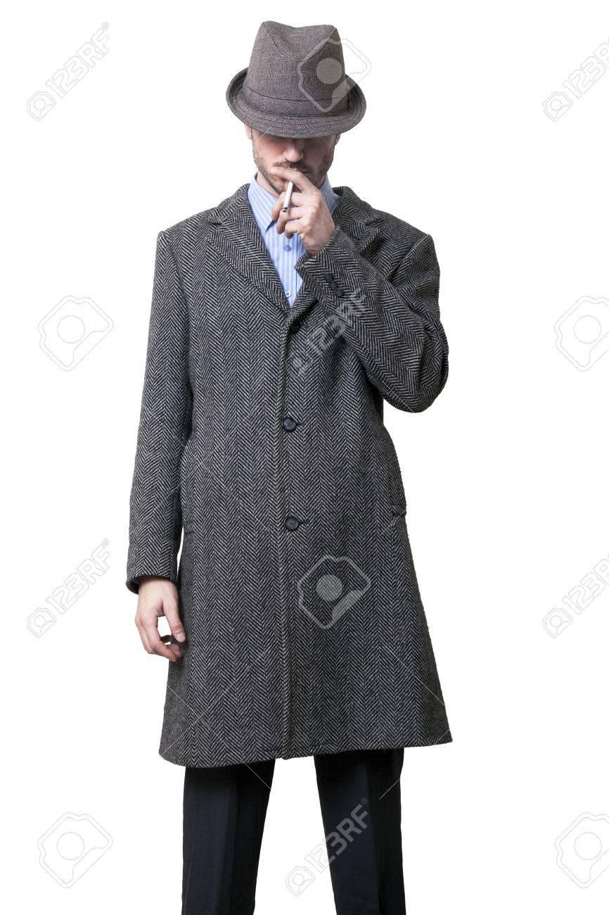 sale retailer 1c19d f817e Una persona vestita con un cappotto grigio e un cappello grigio che è quasi  completamente nascosto i suoi occhi. Fumare una sigaretta. Isolato su ...