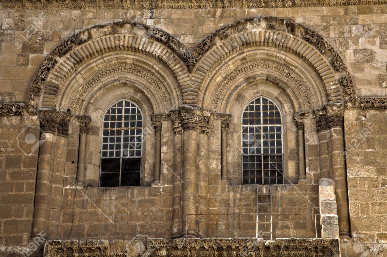 The windows above the entrance to the Church of the Holy Sepulchre in the old city of Jerusalem. This is the place where Jesus Christ was crucified, buried and resurrected, according to the Catholic belief.Just below the right window, the famous ladder o Stock Photo - 19055133