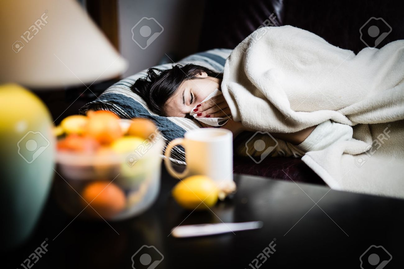 Sick woman in bed,calling in sick,day off from work.Thermometer to check temperature for fever.Vitamins and hot tea in front.Flu.Woman Caught Cold.Virus.Sick woman laying in bed under wool blanket - 52489651