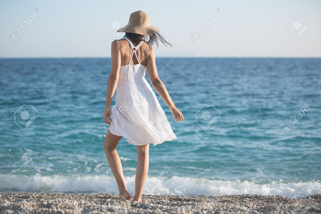 Beautiful Woman In A White Dress Walking On The Beach.Relaxed.. Stock  Photo, Picture And Royalty Free Image. Image 52489873.