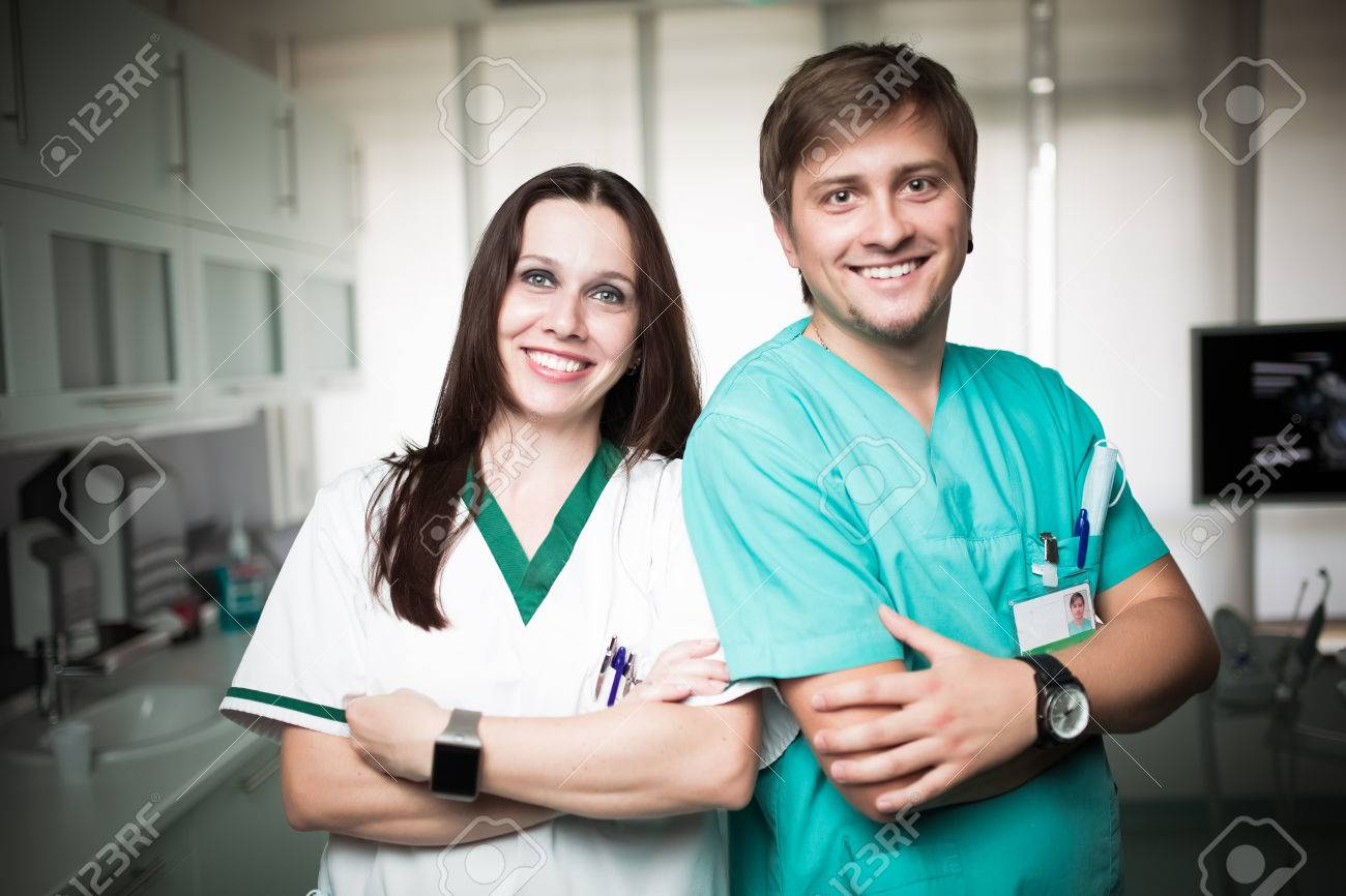 Young experienced doctor dentist standing along with his nurse