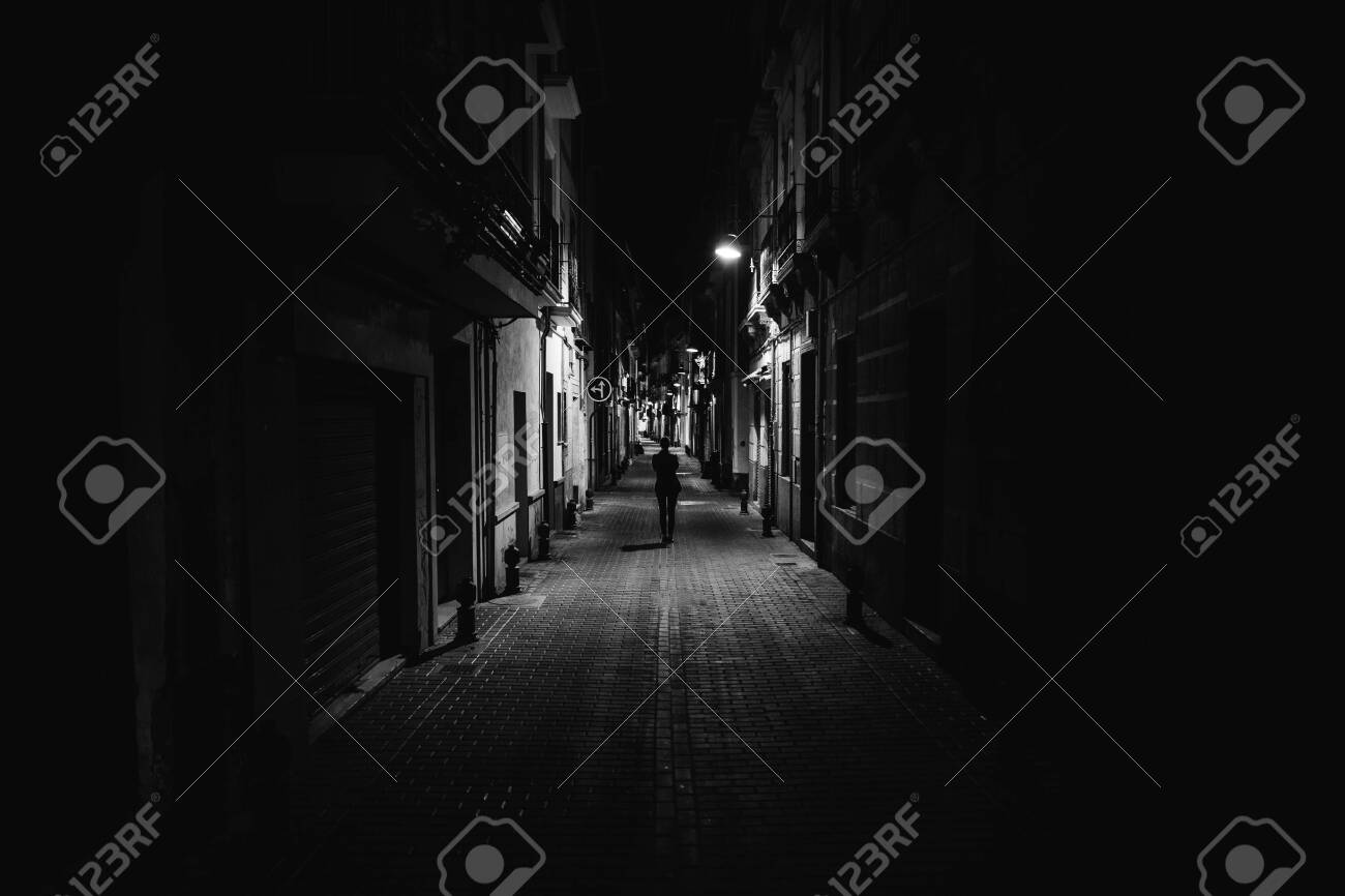 Woman walking alone in the street late at night.Narrow dark alley,unsafe female silhouette.Empty streets.Woman pedestrian alone.Police hour.Assault situation,violence against women concept. - 143139164