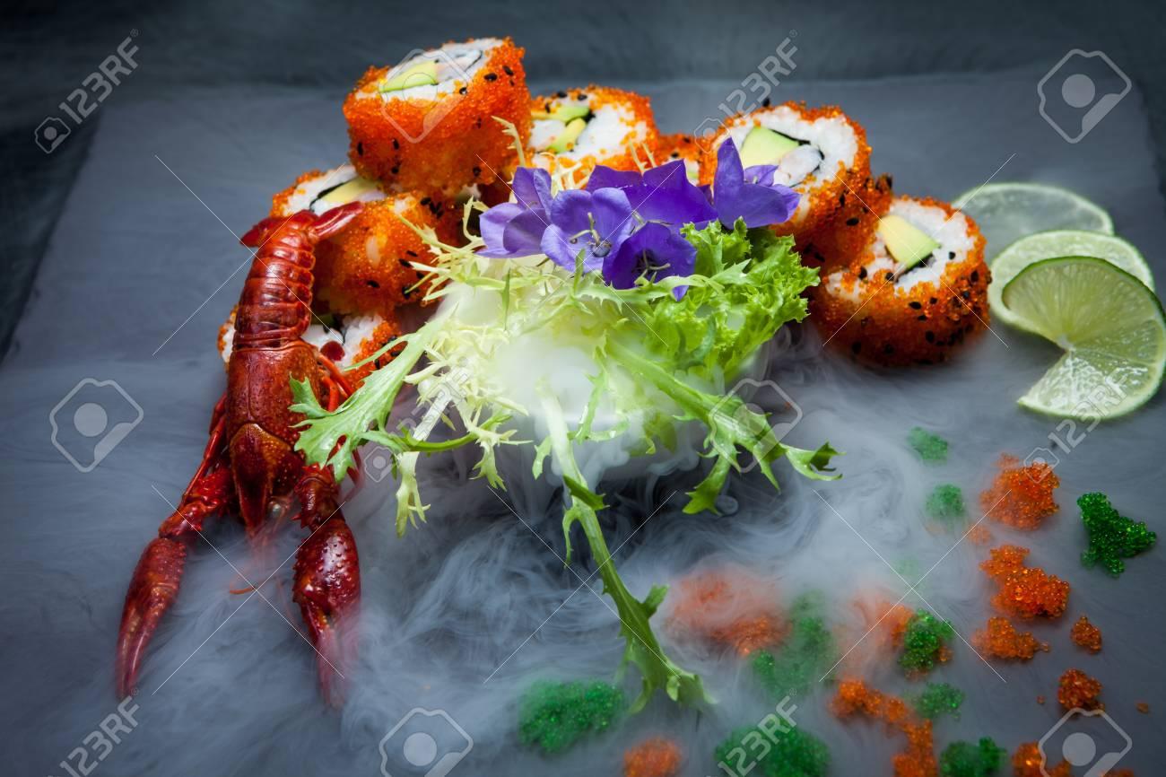 Sea crawfish and sushi on a slate dark plate with liquid smoke
