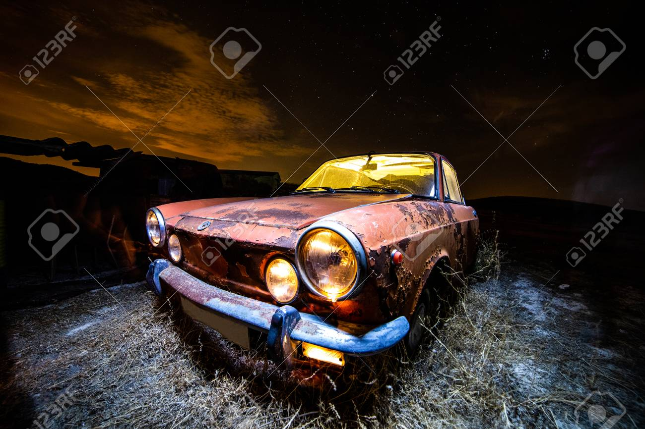 Ancient car abandoned in the countryside and illuminated with lanterns - 109412156