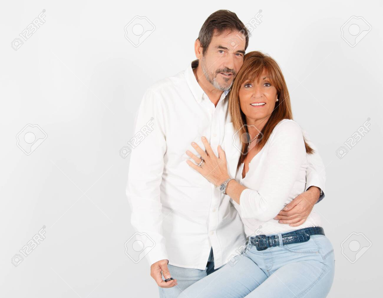 A 50-year-old adult couple poses in a photographic studio in a cheerful way with a white - 131211120