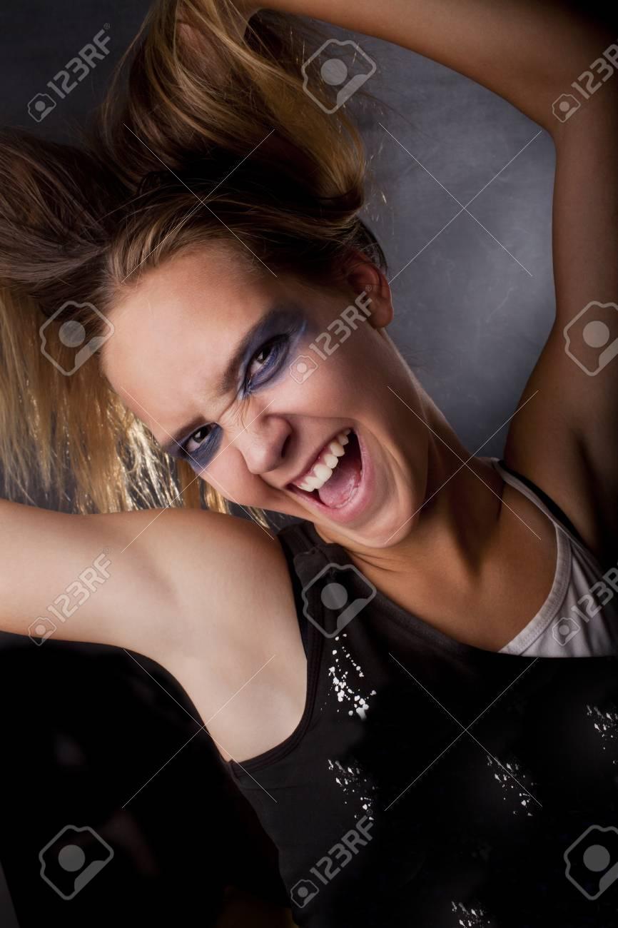 caucasian blond shouting girl holds her hair, on smoke dark background Stock Photo - 12455629