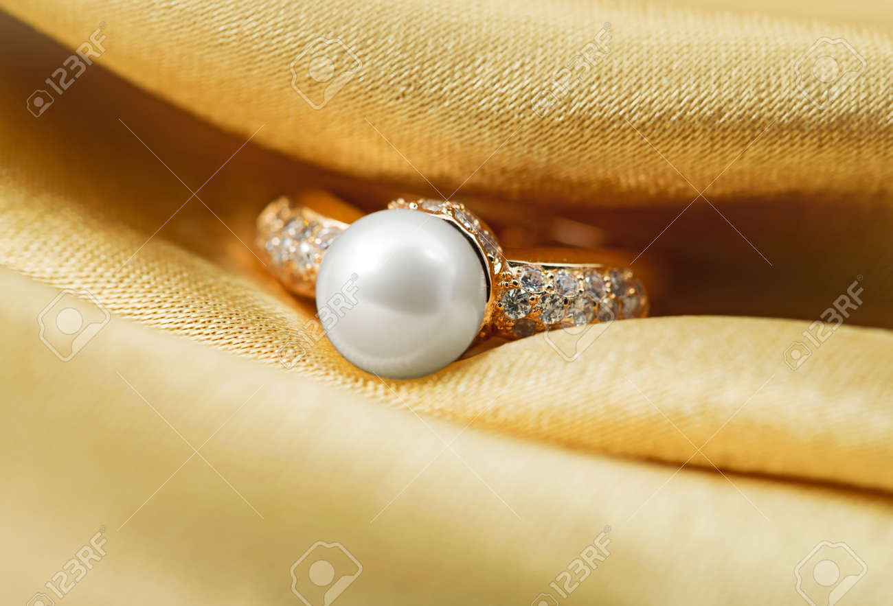 Elegant jewelry ring with jewel stone on a background of golden silk Stock Photo - 8637036