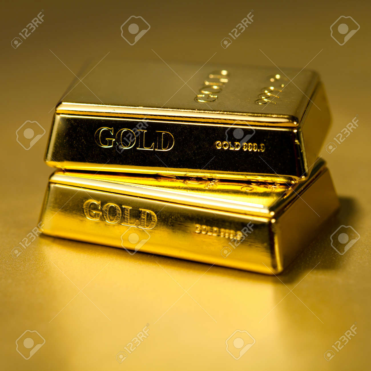 Two Gold bullions on golden background Stock Photo - 13471587
