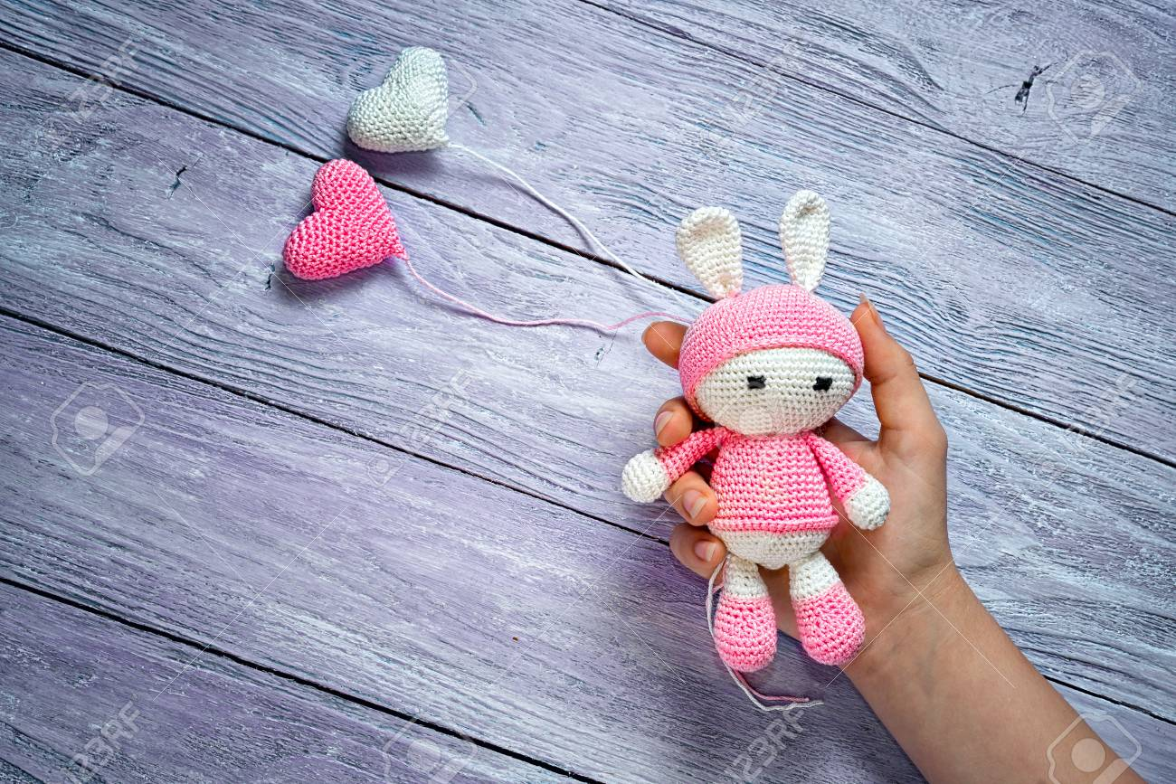 Free Knitted Amigurumi : Children s hand holding a knitted amigurumi toy rabbit and two