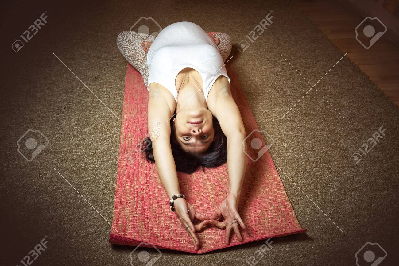 40 week pregnant middle aged caucasian woman sitting in asana doing yoga exercise. Top view, dark colored. Thunderbolt Pose. - 85465048
