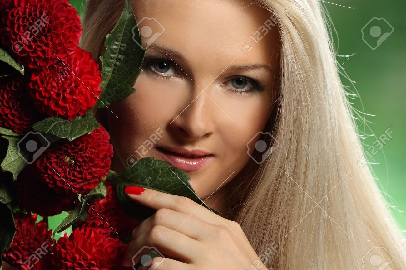 portrait of a young woman with red flowers on green background Stock Photo - 7723896