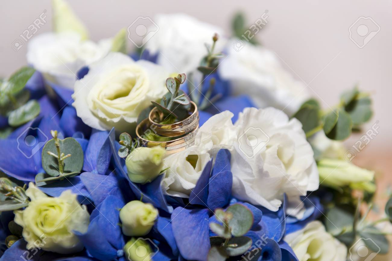 Gold Wedding Rings On A Bouquet Of White And Blue Flowers Bridal