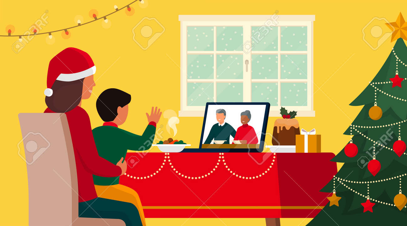 Families celebrating Christmas at home and connecting online on video call, the child is waving at the grandparents on the laptop screen while having lunch - 161454420
