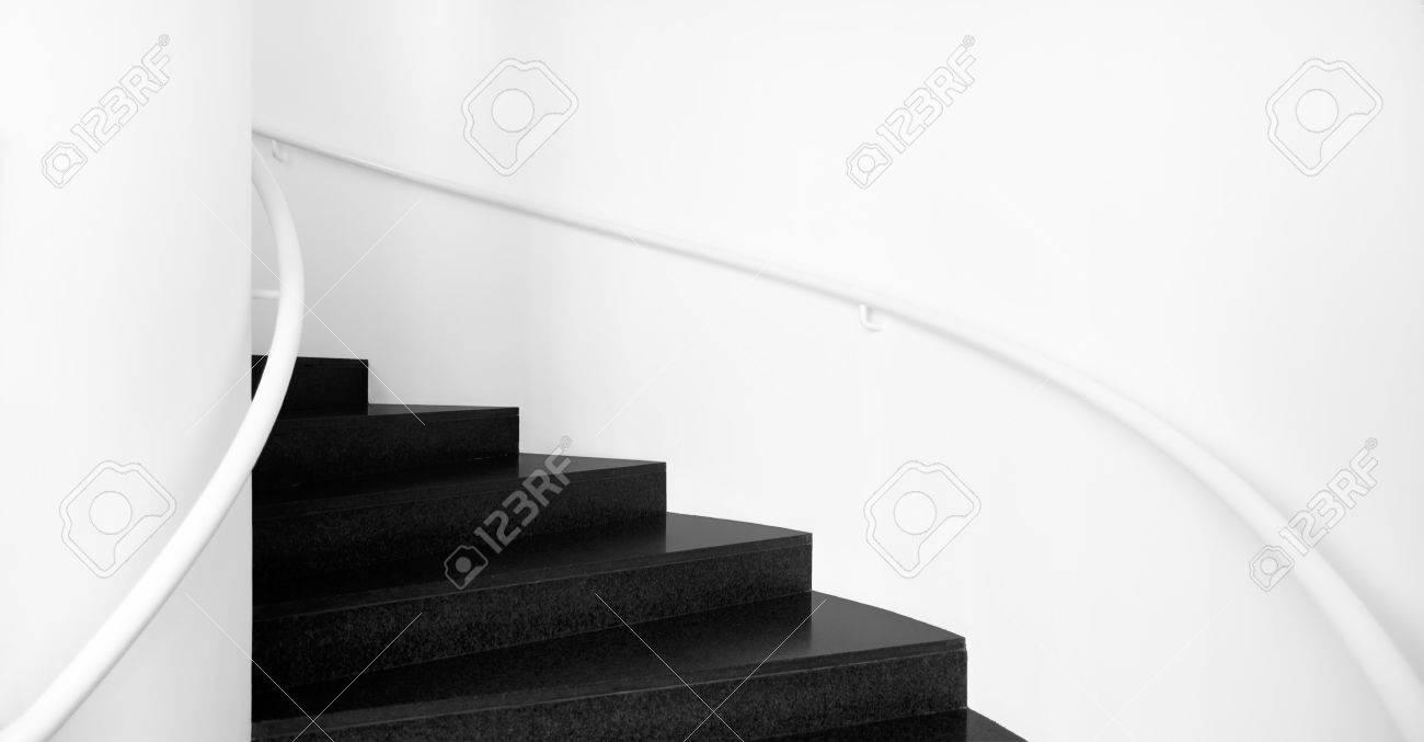Spiraltrappor mellan vita väggar och svarta golv interiör trappor ...