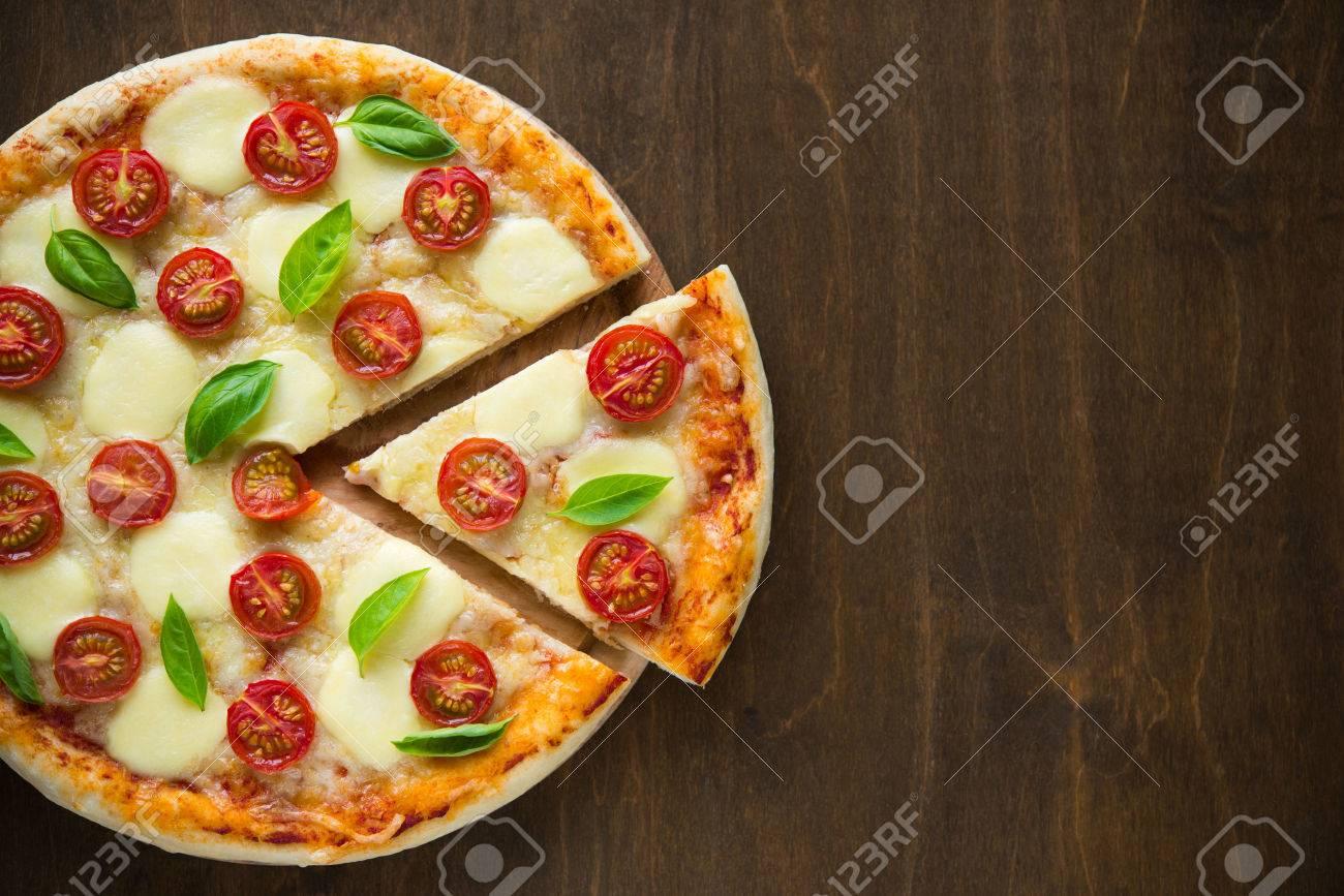 Pizza Margherita on dark wooden background top view - 31900412