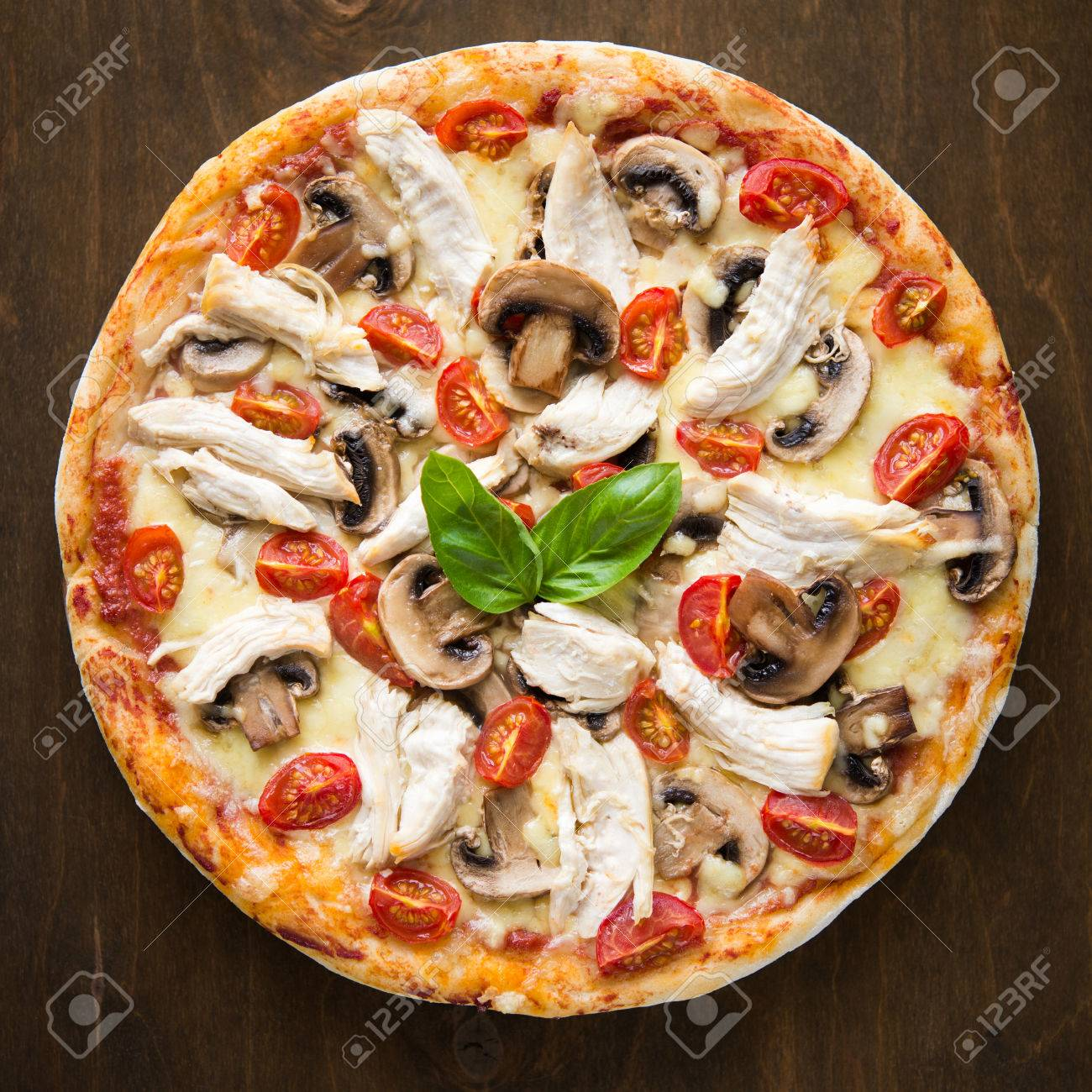 Pizza with chicken, tomato and mushrooms on dark background top view - 32132765