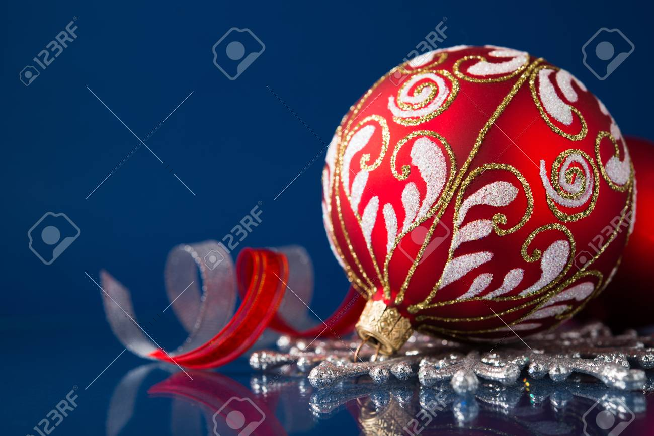 Red and silver christmas ornaments on dark blue xmas background with space for text - 32790777