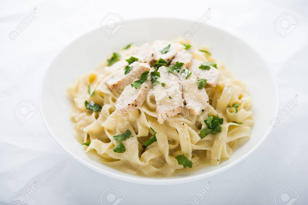 Pasta fettuccine alfredo with chicken, parmesan and parsley on white background close up. Italian cuisine. - 53193131