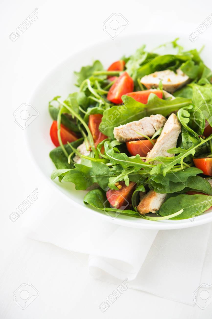 Fresh salad with chicken, tomato and greens (spinach, arugula) on white background close up. Healthy food. - 53193795