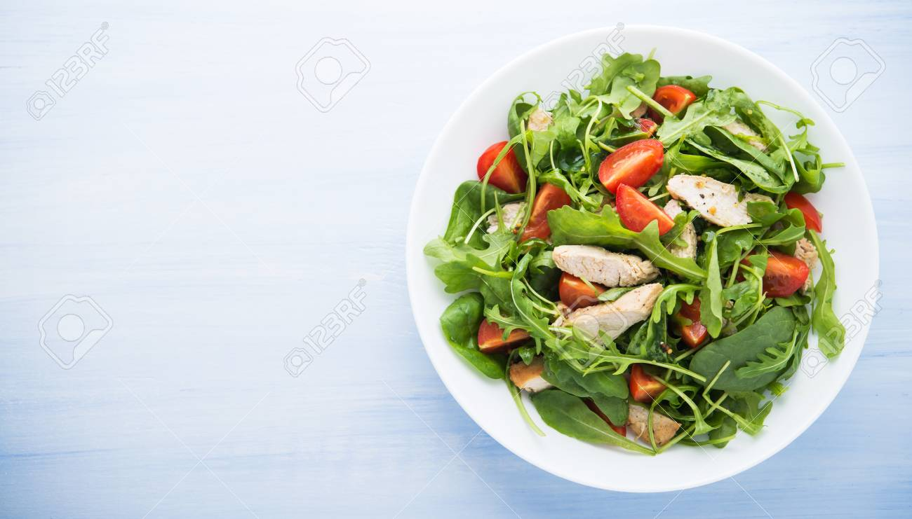 Fresh salad with chicken, tomato and greens (spinach, arugula) on blue wooden background top view. Healthy food. Space for text. - 53193802