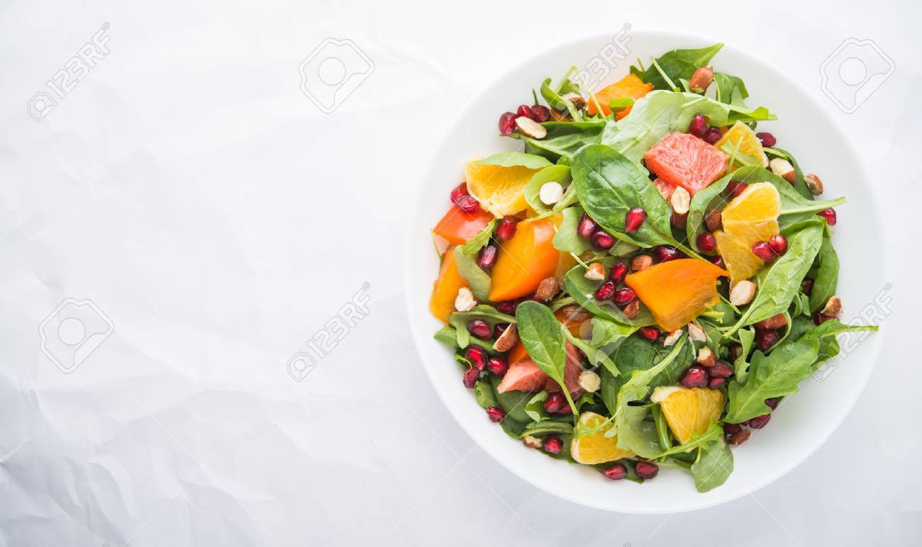 Fresh salad with fruits and greens on white background top view with space for text. Healthy food. - 53194077