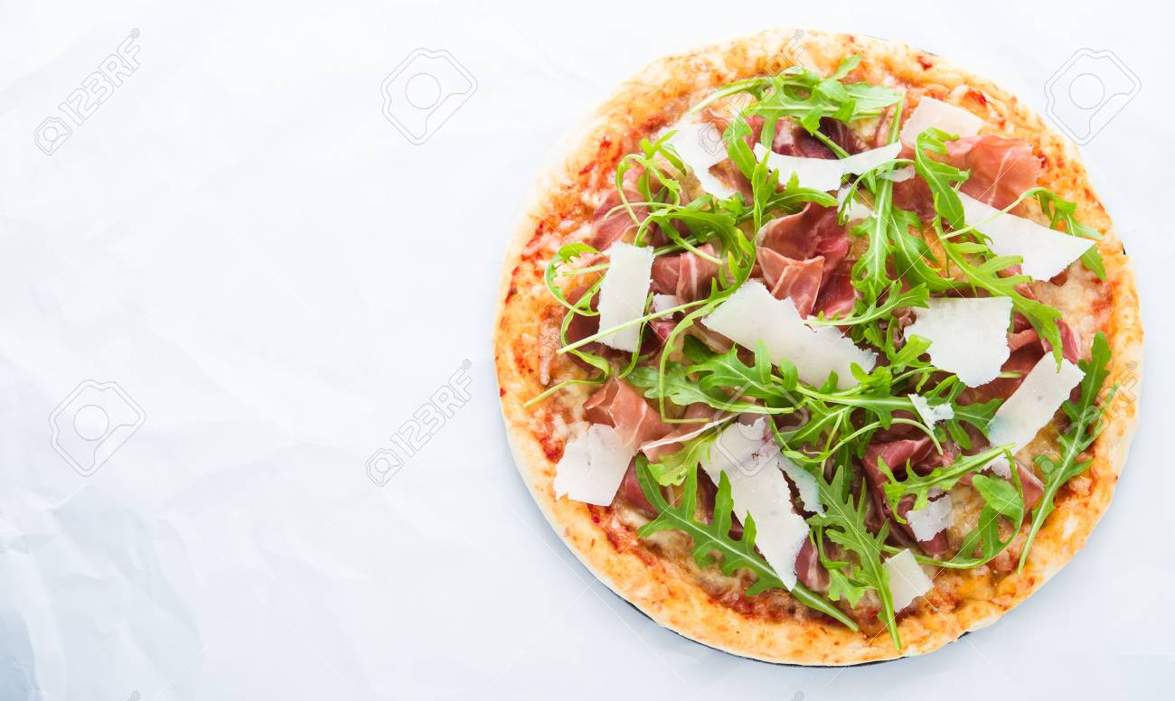 Pizza with prosciutto (parma ham), arugula (salad rocket) and parmesan on white background top view. Italian cuisine. Space for text. - 62705778