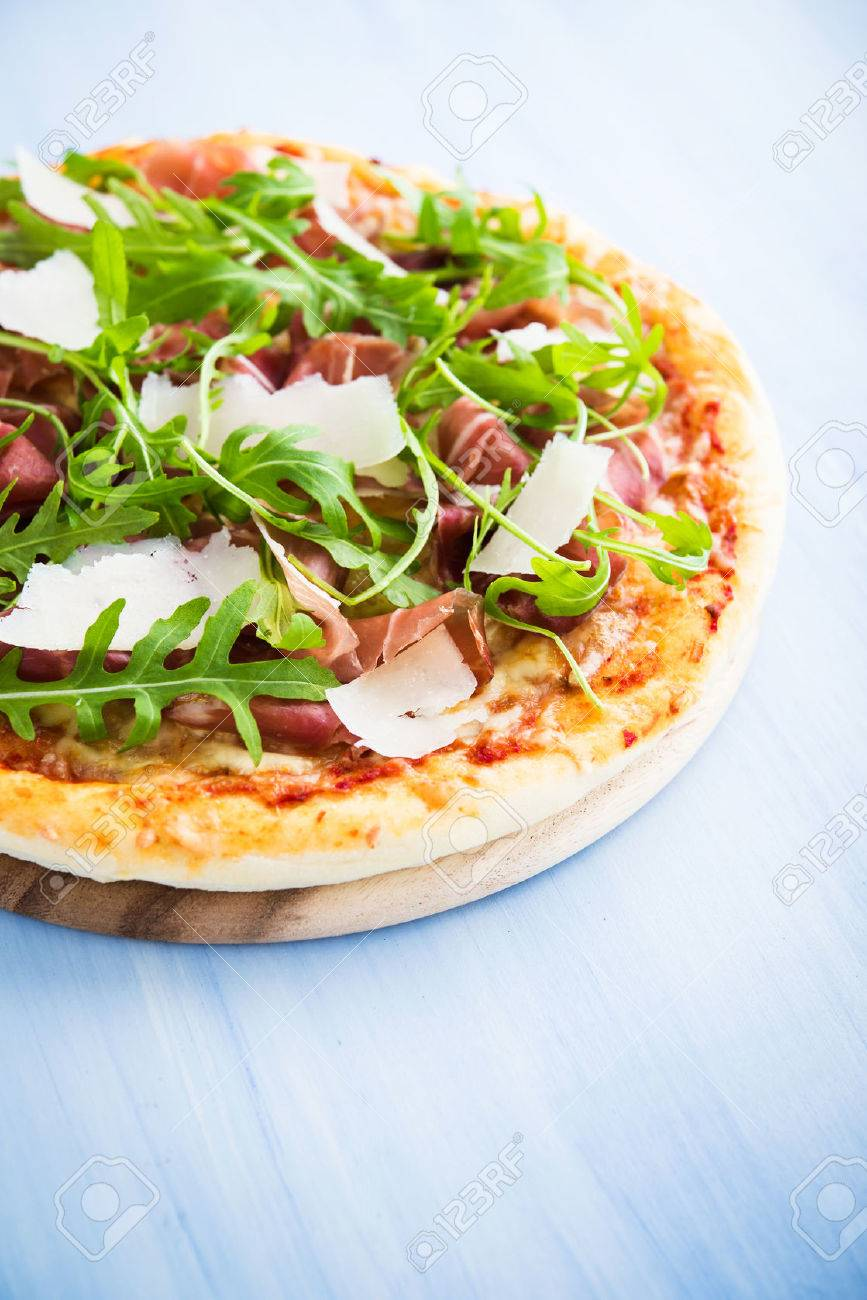 Pizza with prosciutto (parma ham), arugula (salad rocket) and parmesan on blue wooden background close up. Italian cuisine. - 62705780