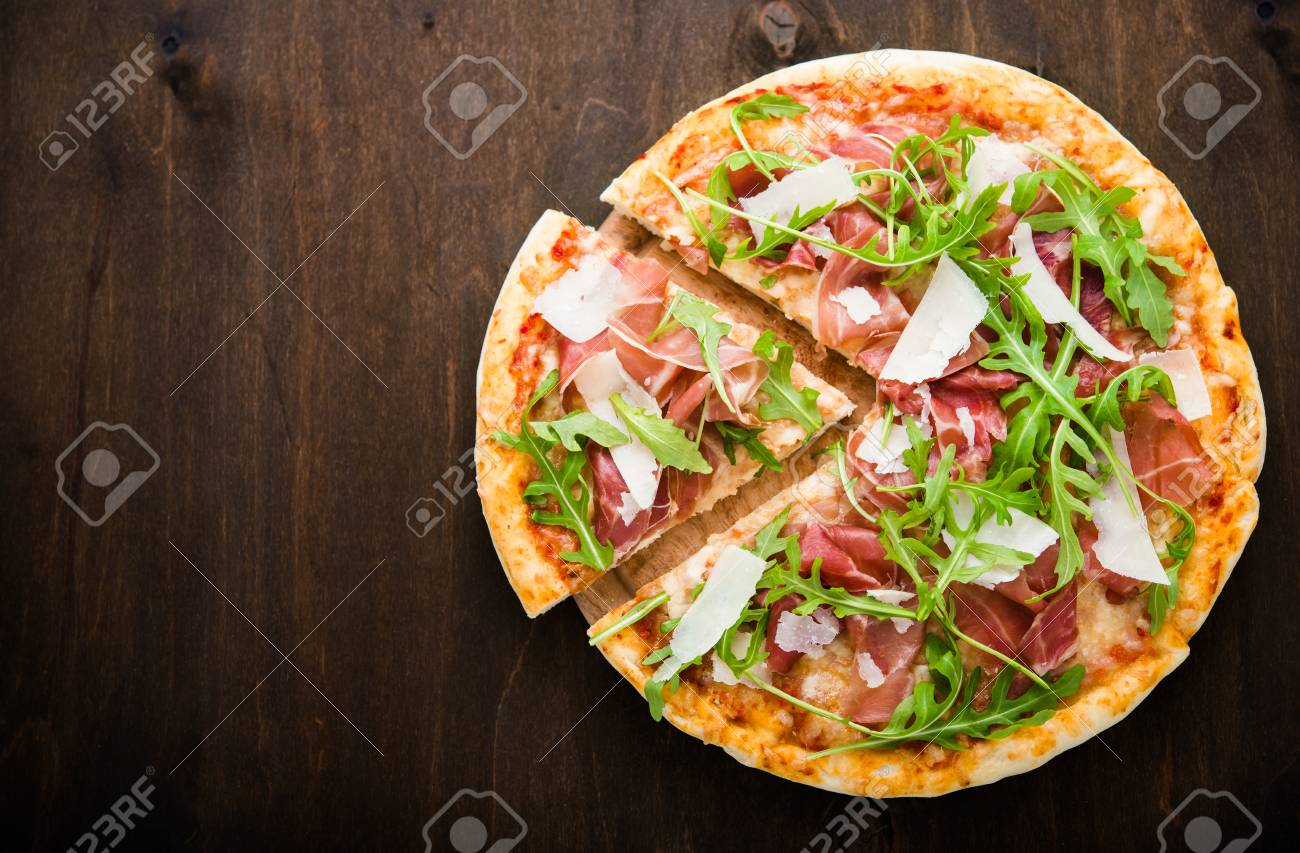 Sliced pizza with prosciutto (parma ham), arugula (salad rocket) and parmesan on dark wooden background top view. Italian cuisine. Space for text. - 62705786