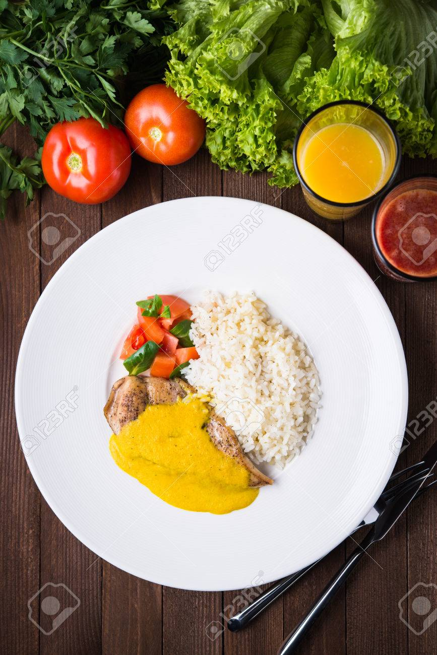 Chicken curry with white rice and vegetables in a plate on dark wood background top view. - 65894227