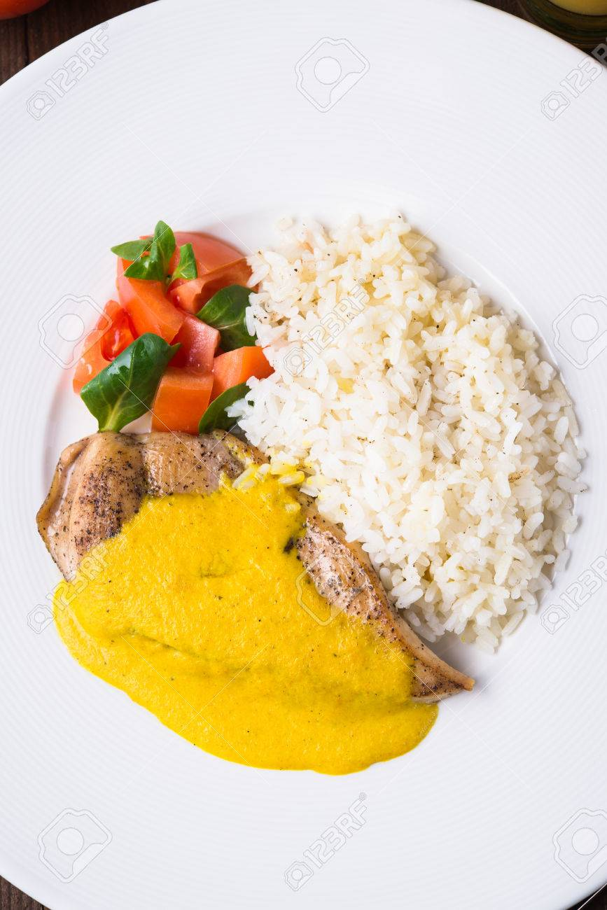 Chicken curry with white rice and vegetables in a plate on dark wood background top view. - 65894241