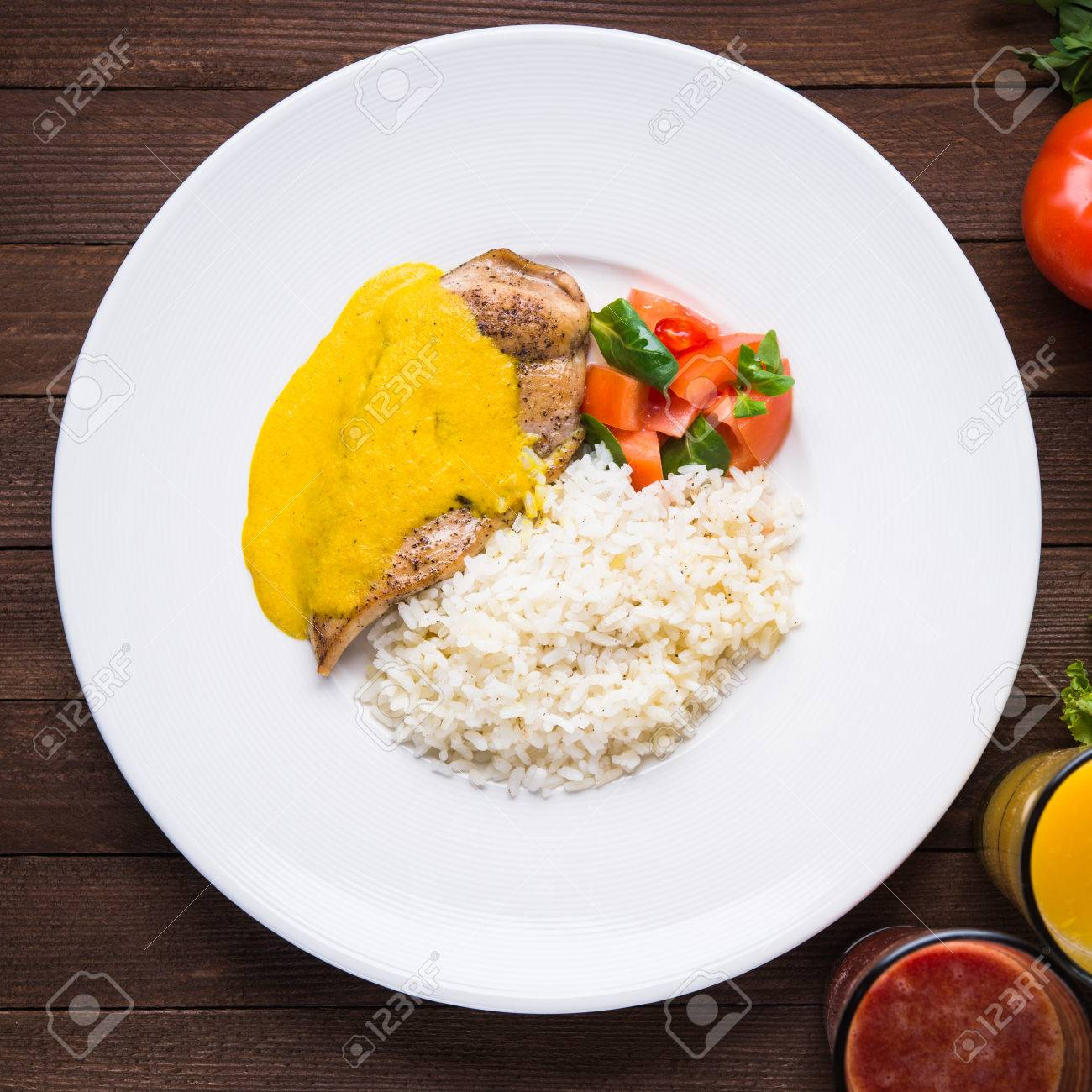 Chicken curry with white rice and vegetables in a plate on dark wood background top view. - 65894225