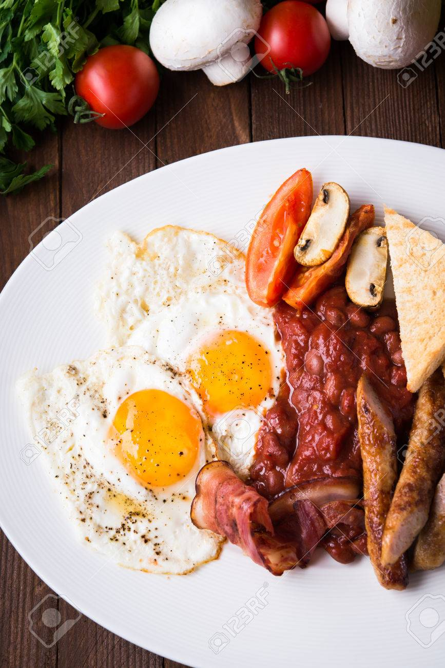 English breakfast (fried eggs, beans, roasted bacon, sausages and vegetables) on dark wood background top view. - 65894053