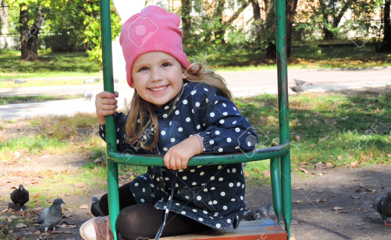 little girl child in autumn clothes and a pink hat in the park swinging on a swing and laughing - 161365315