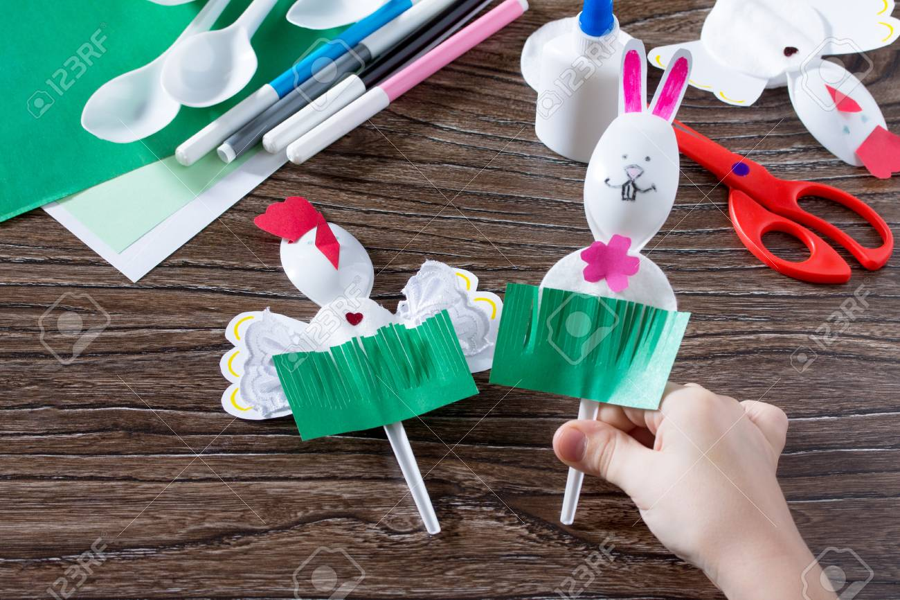 The child creates an easter gift toy easter bunny paper glue stock photo the child creates an easter gift toy easter bunny paper glue and plastic spoons on a wooden table made by hand negle Gallery