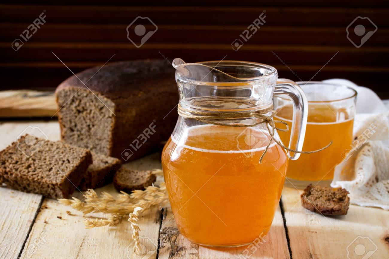 Stock Photo - Traditional Russian cold rye drink Kvas in a glass and a jug  on the kitchen table in a rustic style. Kvass from bread, rye malt, ...