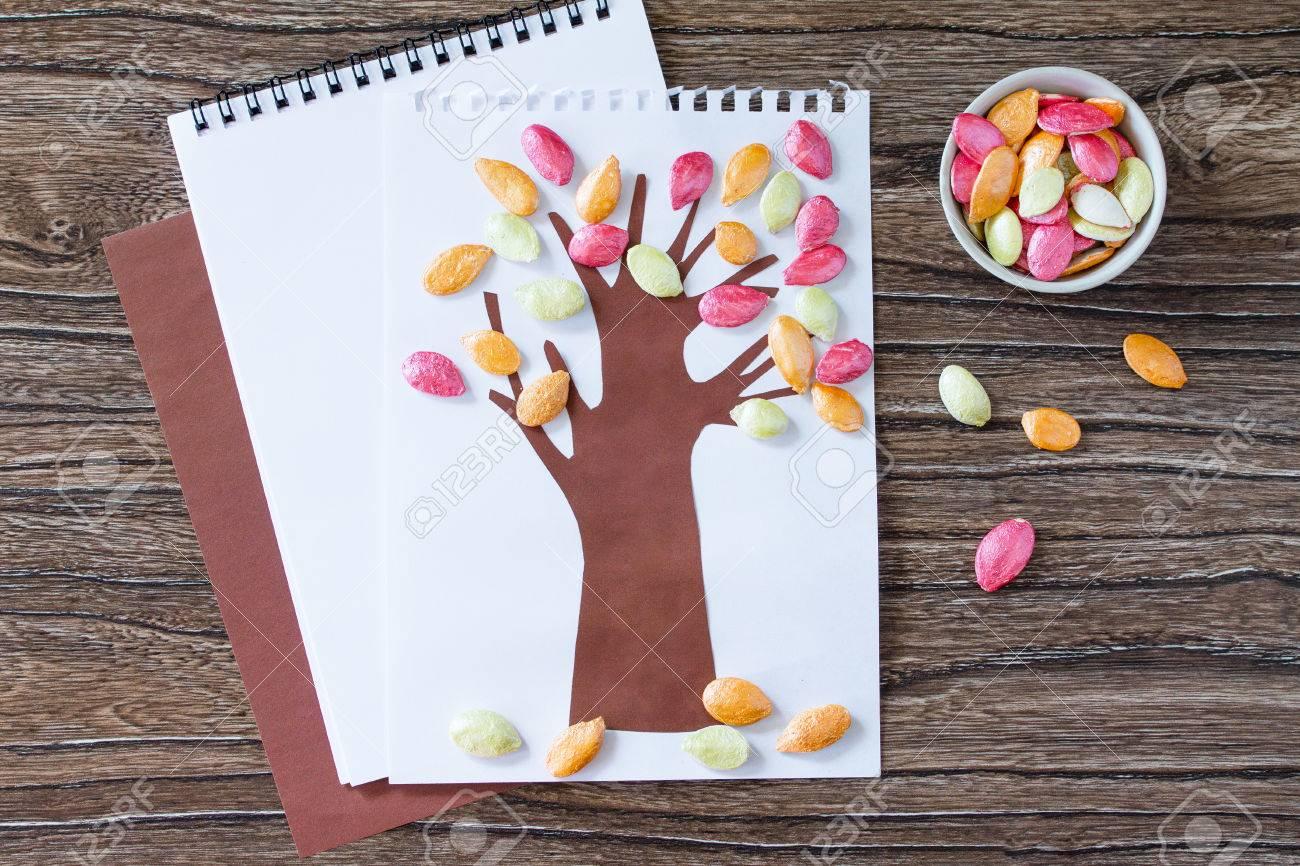 bilder aus kuerbiskernen mit kindern basteln, herbstbaum mit bunten verschiedenen blättern kürbiskerne auf einem, Design ideen