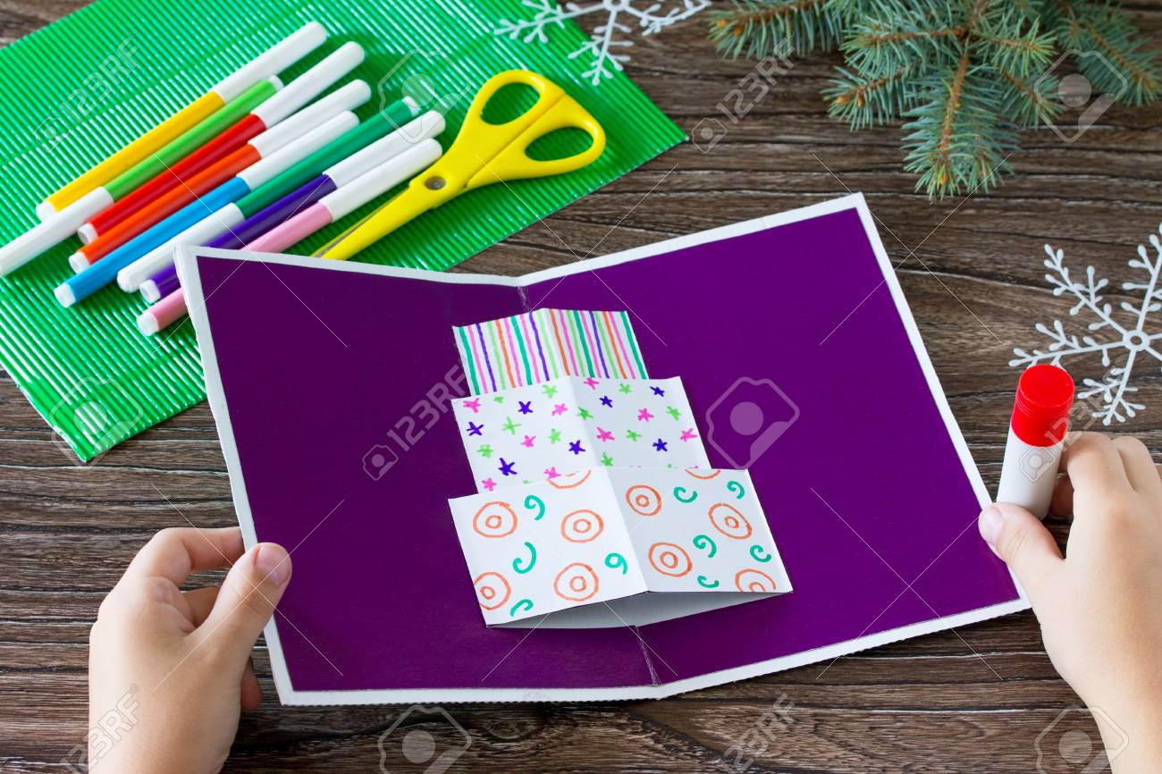 A Child Glues Together A Greeting Card With Christmas Presents