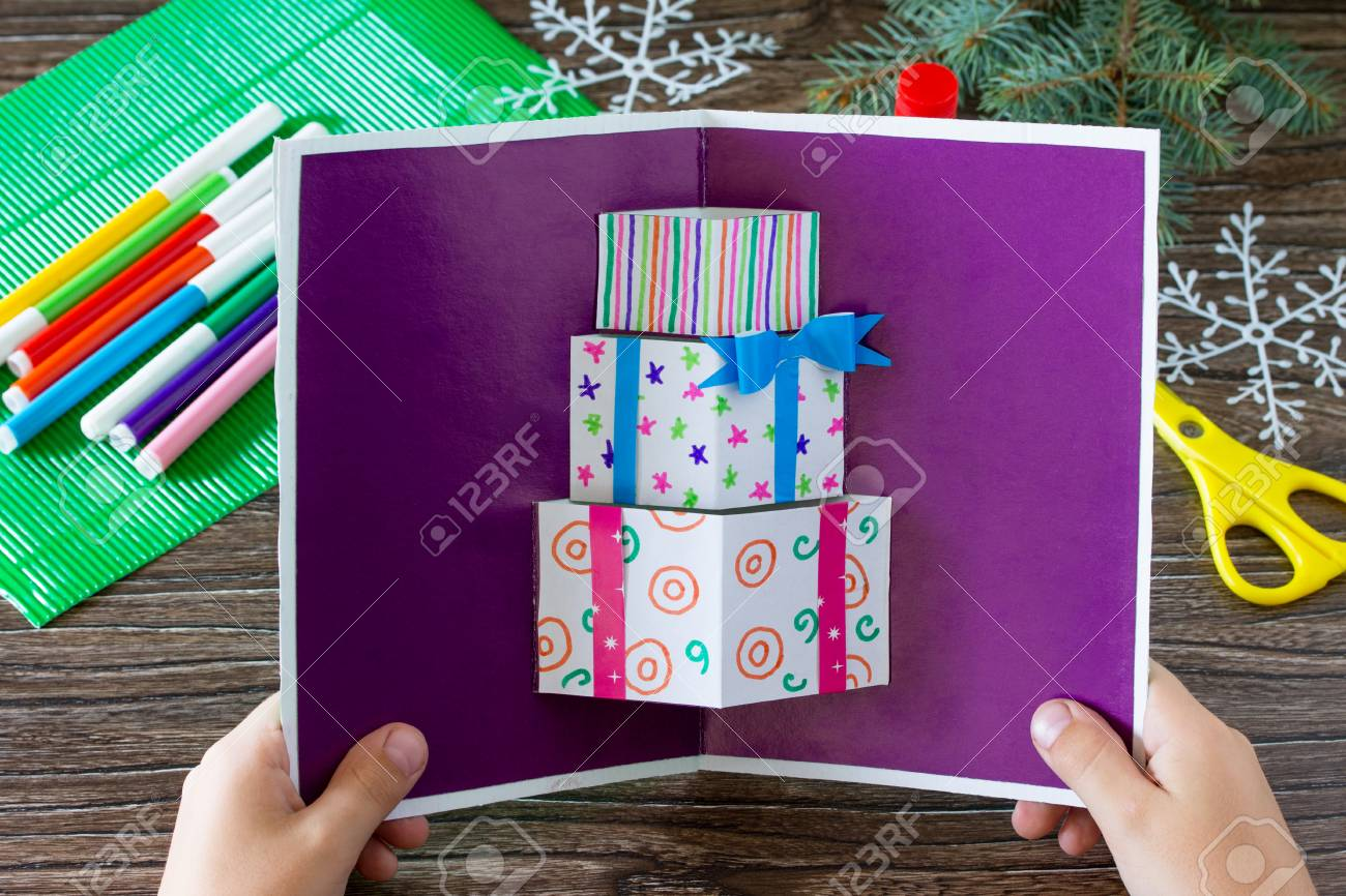 A Child Holds A Birthday Card With Christmas Presents. Made By ...
