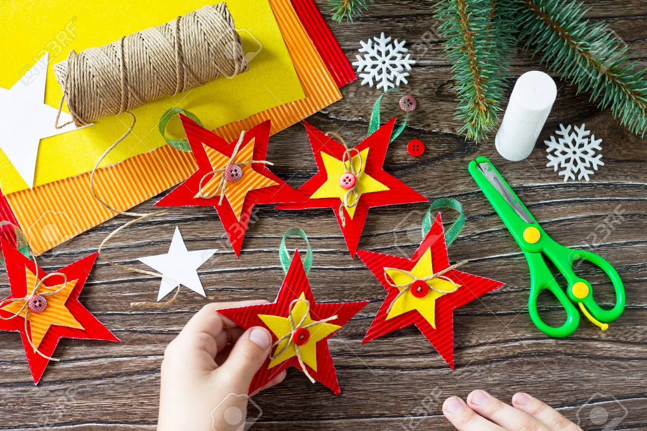 Christmas Tree Toys Handmade.A Child Is Holding Christmas Tree Toys Star Gift Handmade Project