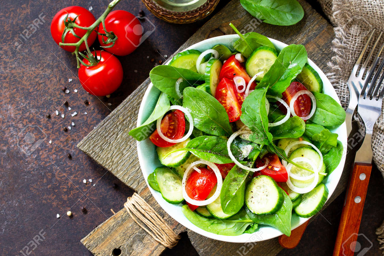 Vitamin snack. Salad with fresh vegetables and spinach on a dark stone or concrete table. Free space for your text. Top view flat lay background. - 126189218