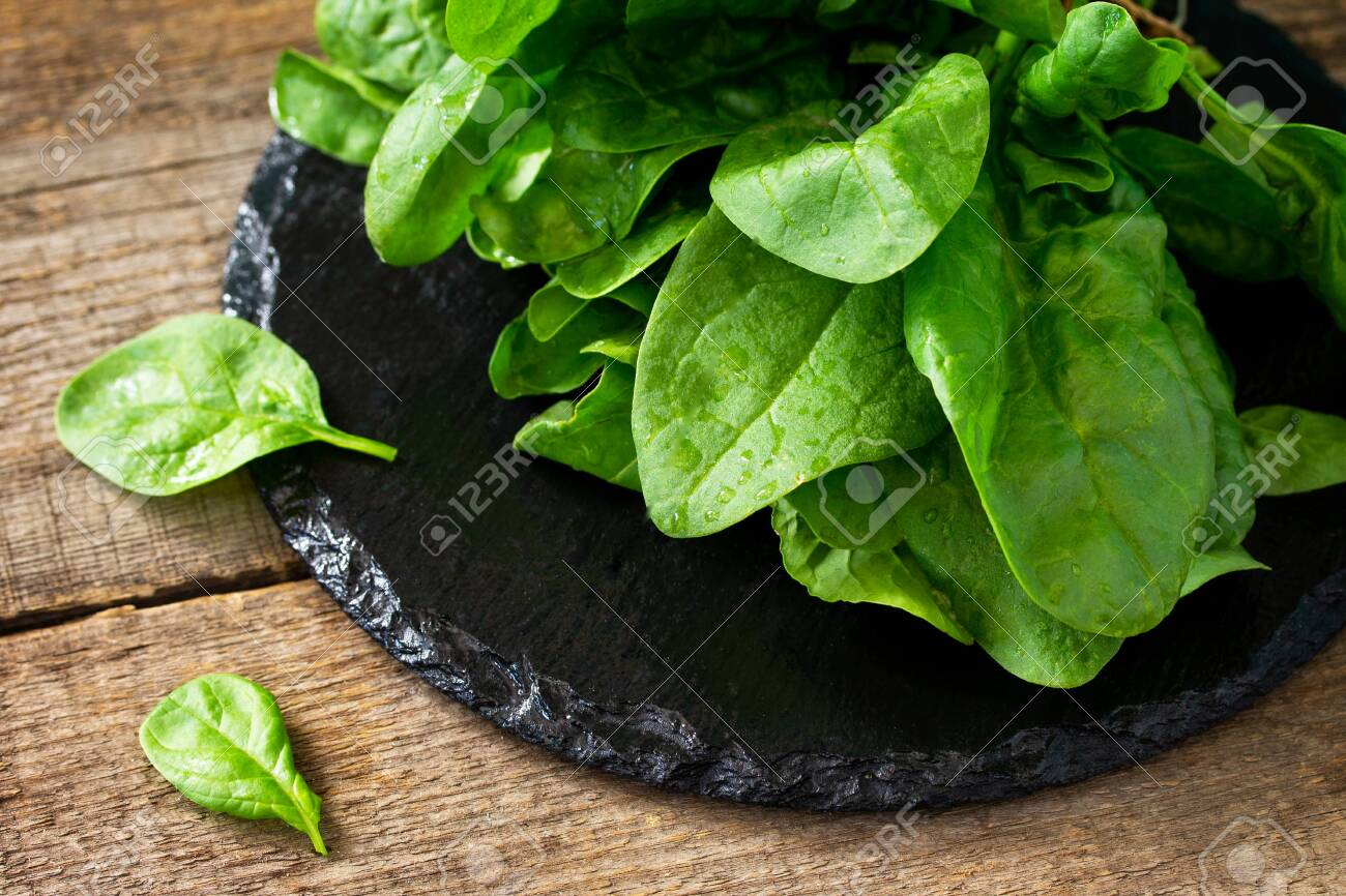 Fresh salad spinach leaves on the wooden kitchen table. - 126531742